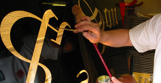 Glass sign being hand painted and guilded with gold leaf.
