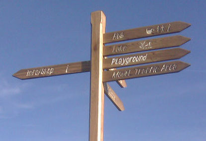 Finger post sign manufactured from reclaimed timber, with infilled lettering.